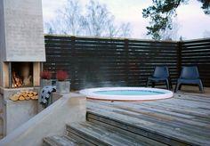 Runt spa-bad nedsänkt trädäck, med insynsskyddade spaljé, betongmur, eldstad