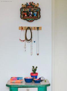 Um cantinho do quarto dedicado para guardar os acessórios. Ideia: use ganchos de parede e bowls para se organizar.