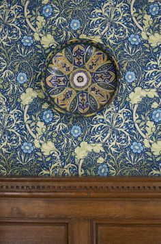 Close view of a ceramic plate against the William Morris-style wallpaper 'Seaweed' and part of the oak panelling in the Inner Hall at Lanhydrock, Cornwall