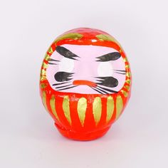 Pre-owned vintage decorative collectible Japanese Daruma or Dharma doll.  Traditional red painted paper mache body with gold accents.  Pink face with blank white eyes and black accents. #EverythingsCollectible #CollectItAll #Daruma #Dharma #Doll #Vintage