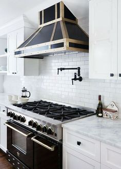 Design Manifest - Black and white kitchen features white cabinets paired with white marble countertops and subway tiled backsplash flanking black kitchen hood with brass trim over oil-rubbed bronze, swing-arm pot filler above BlueStar Range in Black.
