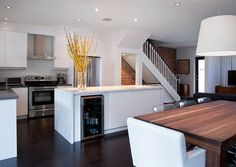 Contemporary kitchen design with white modern kitchen cabinets, charcoal gray Caesarstone Countertops, long kitchen island with calcutta marble countertop, wine fridge in kitchen island, exposed brick wall and espresso stained wood floors.