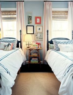 two beds under windows, curtains over blinds, table & photos in between