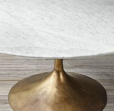 RH's Aero Marble Round Dining Table:Paying homage to the sweeping lines of midcentury furnishings, our table is a study in simplicity. Defined by its balanced proportions and arching, sculptural curves, our interpretation pairs a cast metal pedestal base with a bullnose marble top.