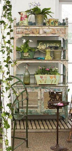 Pretty potting shed with neat chippy paint and plant arrangements.