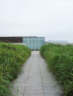tadao ando designs genius loci and glass house for phoenix island, drawing from the rolling landscape to create two spaces of meditation. Genius Loci, Tadao Ando, Glass House, 21st Century, Waterfall, Sidewalk, Sky, Island, Phoenix