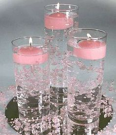 Mirror plate, tall vase, beaded sprays, water and floating candles.