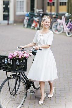 noni 2015 knielanges Brautkleid im 50s Stil mit rundem Ausschnitt, halblangen Ärmeln, Schleife mit Punkten und rosa Petticoat  (www.noni-mode.de - Foto: Le Hai Linh)