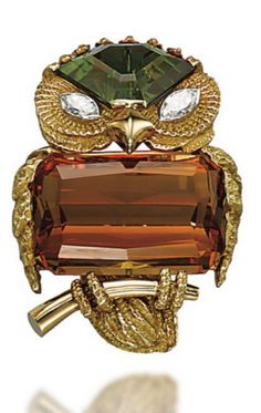 A Citrine, Peridot, Diamond and Gold Owl Brooch, by Cartier – Designed as a sculpted gold owl perched on a branch, the body set with a rectangular step-cut citrine, the head as a fancy-shaped peridot with marquise-shaped diamond eyes, 1950s, 4.5 cm, in red leather fitted Cartier case Signed Cartier.