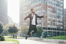 Young handsome contemporary business man jumping outdoor in city back light…