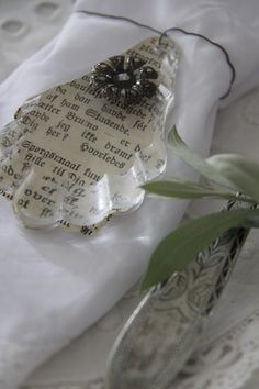 Mod podge newspaper or print to the back of a crystal for an instant personalized Christmas ornament or gift bow.