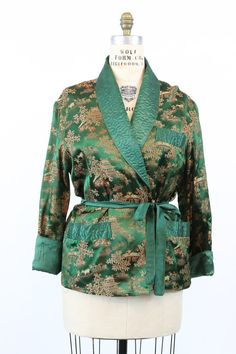 Gorgeous 1950s Asian robe! Made in a stunning forest green satin that is fully embossed with a stunning novelty Asian farming print. Collar and