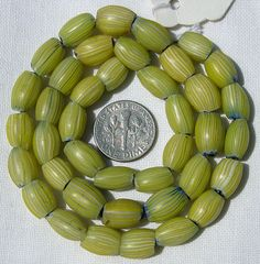 Africa Trade Beads | A strand of Venetian, oval, four layer beads, known as onion skin. They date from the late 1800`s to the early 1900`s. | The layers, from the core outwards, are blue, white, blue and yellow and translucent.