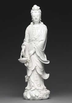 A LARGE DEHUA STANDING FIGURE OF GUANYIN QING DYNASTY, 18TH CENTURY finely modeled standing on a lotus leaf base above cresting waves, wearing a long robe tied at the waist and open at the chest revealing a beaded necklace, the hair tied in an elaborate topknot behind a tiara, the left hand holding the skirt hem, right hand holding a wicker basket, the back with an impressed Wanli six-character mark within a square below an impressed double-gourd seal bearing the characters Fujian Dehua…