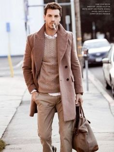 Men's Camel Overcoat, Tan Cable Sweater, White Longsleeve Shirt, Khaki Chinos, and Brown Canvas Holdall