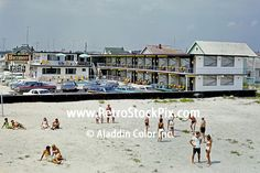 Buccaneer Motel, North Wildwood, NJ. Families playing and lounging on the beach in front of the motel.