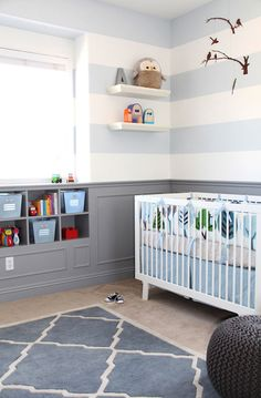 striped walls + clean modern lines on crib + built in shelving. awesome nursery.