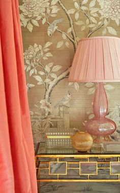 Bedroom Detail: Coral pink silk taffeta curtains, khaki Chinoiserie wallpaper, gold leaf table, & colored glass accessories. Designed by Nancy Pearson.