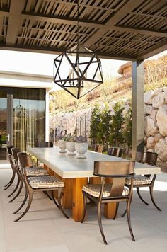 Amazing covered patio featuring iron and glass polyhedron pendant over rectangular outdoor dining table surrounded by glossy black klismos chairs with Greek key cushions.