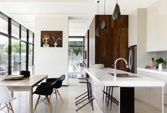 Doherty Lynch's Swinburne Avenue kitchen. Bronze mirror, spotted gum cladding and dark framed windows.