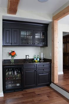 The wet bar includes custom cabinetry, a Bronzo Quartzite countertop, and a hammered copper sink.