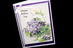 This handmade Mother's Day card is fashioned on a white pearlescent base. On this is a panel of purple pearlescent card and a further one of a printed background of s flower basket. This carries a decoupage of purple flowers with their lush green foliage. There is a printed daisy, which has been lightly glittered, on the handle of the basket. There is a white ribbon and bow on the left of the printed panel. White Ribbon, Flower Basket, Lush Green, Happy Mothers Day, Purple Flowers, Decoupage, Card Ideas, Daisy, Card Making