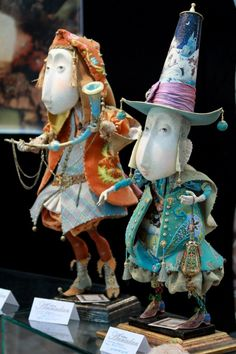 pair of puppets with a layered colorful look. orange one and blue one. long faces, elegant clothes. annadan