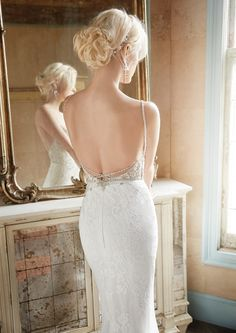 Ivory Lace fluted bridal gown with intricate jeweled embroidery throughout the bodice and hip, low back.