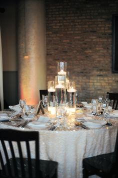 romantic candle wedding centerpiece. Love the gold shimmering wedding reception table cloth.  Photo: Erica Rose Photography