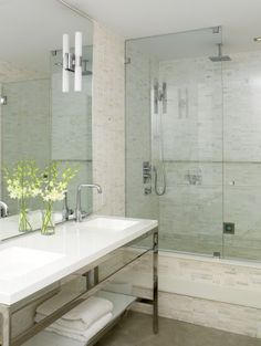 Maximize space with a bright color palette, frameless shower enclosure and open vanity console