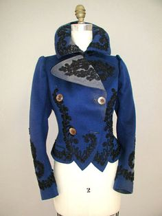 """1895 -1905 Deep Royal Blue womans jacket   The outside of the coat is decorated with black cotton passementerie braid at the front lapels, around the collar edge, down center front, around the hem to the back. Center back has a large motif as well as do the lower edges of sleeve hems. There are two hand finished button holes 1 1/4"""" wide with a set of four mother of pearl buttons that close the double breast."""