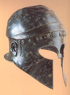 From the Archaeological Museum of Olympia, comes this helmet dated to the 6th century bce. Identified as a Chalcidean helmet, it has several stylized features, such as the curls at the brow and rear, 'locks' of hair on the sides, and ears.