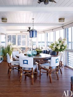 In the sunroom, a bespoke table by Blatt Billiards is grouped with a suite of Bielecky Brothers chairs; the hanging lantern is by Jamb, and the seat cushions are covered in a Rose Tarlow Melrose House fabric | archdigest.com