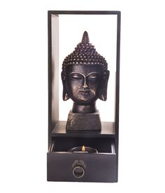 A beautiful piece for your home décor, as it imbibes a classy look. This is a Buddha head placed on a rectangular rack. It has a drawer with spcae for teal light holder. The collection of small smooth pebbles give a raw beauty to this piece.