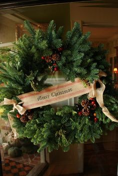 """Decorate a wreath with pine cones, berries, and upholstery webbing + stencil letters """"Merry Christmas"""" with a magic marker.  Use a suction cup holder from http://www.swisco.com/Giant-Suction-Cup/pd/Decorating-Hardware/14-002 to adhere to glass."""