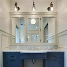 A two-toned color scheme with white above and navy below brightens and adds interest to this vanity area.