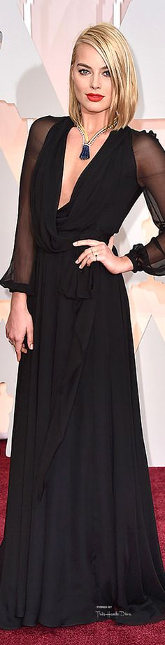 Margot Robbie in a low-cut, black Yves Saint Lauren gown and Van Cleef & Arpels tassel necklace at the 2015 Oscars