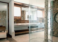 As formas orgânicas deram o tom e o conforto ao banheiro de 25 m². O destaque é o boxe caracol, criado pelo designer Fabio Galeazzo. A madeira de demolição cobre a parede e o teto acima da bancada  (Foto: Edu Castello)