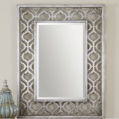 Instantly enliven any ensemble in a pinch with this eye-catching wall mirror. It is crafted from manufactured wood and offers up an elegant openwork trellis motif. Chic simply shining solo, this piece is even more vibrant when surrounded by a collection of colorful canvas prints or a pair of glowing wall sconces. Hang it up above a weathered wood console table topped with glowing lanterns for a splash of bohemian style in the entryway, or pair it with a plush Chesterfield sofa studded with…