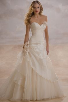 This is a romantic Organza wedding gown with clusters of flowers embellished on bodice and side waistline. Asymmetrically pleated sweetheart bodice is ultra feminine as well as curve showing. Side-drape organza is gathered with a remarkable cluster of blossom, and covers half of the tulle A-line skirt. Shown in ivory. More colors are available as in Color Options. Custom-measurement for any sizes.