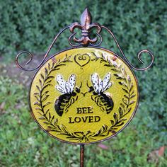 One of a set of three retro garden stakes with a bee theme. Glass and metal construction.