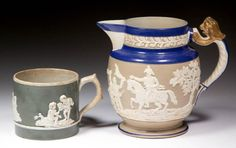 "ENGLISH CERAMIC ARTICLES, LOT OF TWO,  comprising one small smear-glazed jug having a light brown body, white sprig-molded design including ""WELLINGTON"" on horseback, blue slip on base, shoulder, and rim, X on base executed in blue pigment; one small pearlware mug with deep green slip ground and three white sprig-molded designs, unmarked. Staffordshire and other areas."