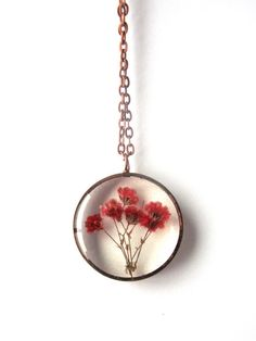 Encased in jewelers grade resin are several dyed red babys breath flowers! The copper pipe bezel is handmade by me and has an antique copper finish. It would make a great gift for the flower lover in your life!  The pendant measures 1 1/4 round by 3/8 deep.  Included is a 24 antique copper color vintage style metal chain with a lobster clasp.  The listing photos are representative of the item you will receive. Just as in nature, no two items are identical. However each pendant is gu...