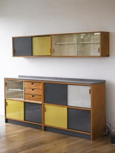 Cabinets and cupboards of glass, wood, yellow and gray... I don't think this is my style, but it's way cool. Especially if the gray parts are chalkboards.