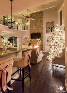 Two story christmas living room with glowing christmas lights #barstooldecor #christmaslivingroom #greatroom #glowingchristmastree