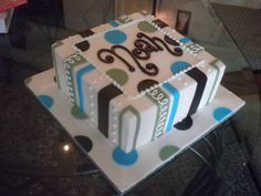 10-inch square cake iced in white buttercream with green, brown, and blue fondant dots and stripes.