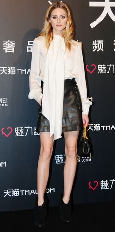 For a visit to Shanghai, Olivia Palermo edged up her elegant cream tie-neck blouse with a studded leather mini and black booties.