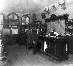 . Interior view of the Toll Gate Saloon, Black Hawk, Colorado; shows arched entry windows, swinging front doors, stove in front left foreground, wooden floor with stains, and calendar from 1897 on entryway wall. Three men occupy the saloon. One bartender stands behind the bar; two others stand in front of the bar. The man in the foreground has his foot on the bar rail and holds a cigar. The man to the rear is leans on the bar and holds a beer in his right hand.  1897
