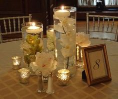 Varying heights of glass cylinders filled with orchids and floating candles