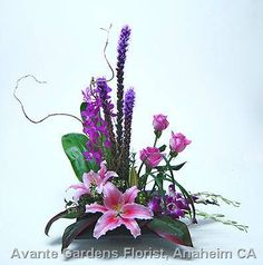 An Ikebana influence design in a black plateau container featuring roses, liatris, Mokara orchids, dendrobium orchids,lilies and tropical foliages.